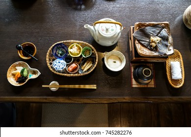 Japanese ryokan breakfast appetizer dishes including  mentaiko, pickle, seaweed, bamboo shoot, hot plate, other side dishes,  green tea pot, cup and warm towel on wooden table, Japan