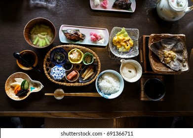 Japanese ryokan breakfast dishes including cooked white rice, grilled fish, fried egg, soup, mentaiko, pickle, seaweed, hot plate, other side dishes and green tea on wooden table, Japan