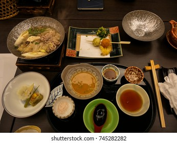 Japanese ryokan kaiseki dinner main dish including pork shabu hot pot, variety of vegetables, with salt and sesame vinegar sauce, side dishes and fried food of spring, Japan