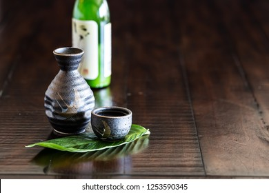 Japanese Sake and sake cups on the wooden table.