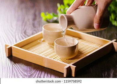 Japanese sake pouring scene to the white cup with wooden tray and brown desk