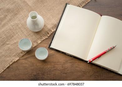 Japanese SAKE in white bottle on wooden desk with note book