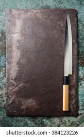 Japanese sashimi knife on black stone slate background texture