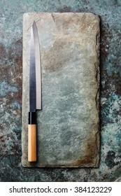 Japanese sashimi knife on gray stone slate background texture