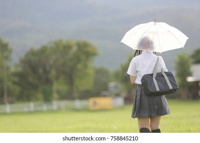 Japanese school girl with umbrella on rain in countryside with grass mountain and tree