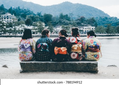 Japanese School Girls sitting together in colourful kimono traditional costume, Miyajima, Japan