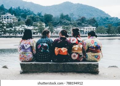 Japanese School Girls sitting together in colourful kimono traditional costume, Miyajima, Japan
