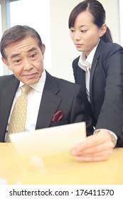 Japanese Secretary showing notes to her boss