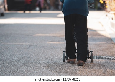 Japanese senior with a walking disability walking on street pushing her walker or wheel chair.