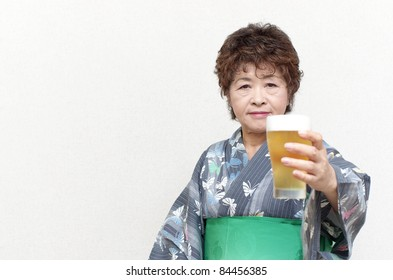 Japanese senior woman putting up glass of beer
