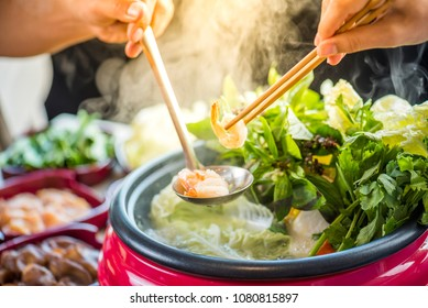 Japanese Shabu Shabu and Sukiyaki in hot pot at   restaurant.Japanese food are high quality food cooking in hot boil soup with vegetable beef raw meat or sea food hold with chopsticks