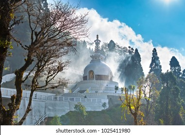 Japanese shanti-stupa, aka Peace pagoda, on the top of mountain in the Darjeeling, in a haze of the arising clouds which penetrate sunshine.