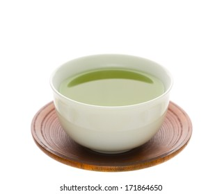 Japanese simmered green tea in a ceramic cup on a traditional wooden saucer isolated on white with copy space