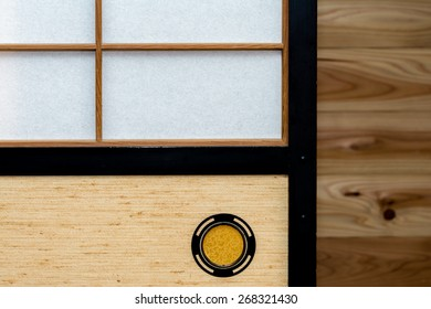 "A Japanese sliding door called ""shoji"" or ""fusuma"" with a wooden wall in the background."