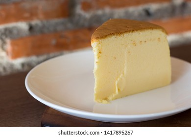 Japanese soft butter cake in white plate on wooden table with copy space.