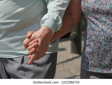 a Japanese soulmate couple holding hands and walking together on sunny day.