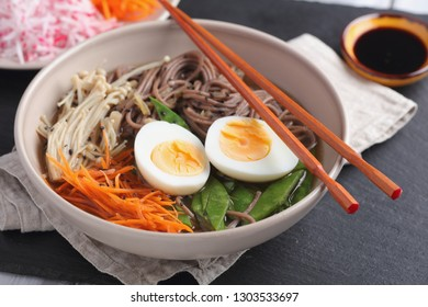 Japanese soup with Enoki mushrooms, soba noodles, boiled egg, carrot, radish, green beans, and soy sauce
