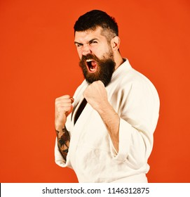 Japanese sports and martial arts concept. Young sporty man in white kimono isolated on red background. Athlete with beard and raging face holds fists in defence.