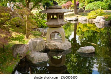 Japanese statue of a house on the small pond in the park.