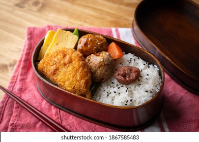 japanese style bento in wooden box with meat ball and croquette