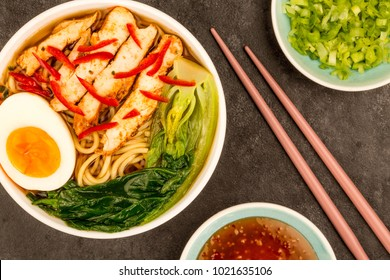 Japanese Style Chicken And Chilli Ramen Soup or Broth With Pak Choi Against A Black Table Top