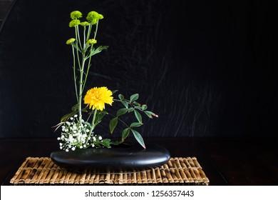 Japanese style flower arrangement ikebana isolated on black background