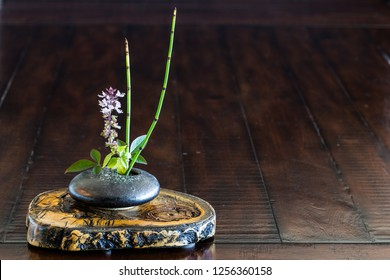 Japanese style flower arrangement Ikebana isolated on rustic table.