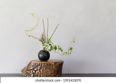 Japanese style flower arrangement Ikebana on gray background