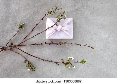 Japanese style gift box (Furoshiki) and blooming cherry branch on concrete background.