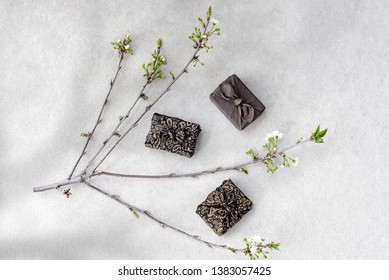 Japanese style gift boxes (Furoshiki) and blooming cherry branch on concrete background.