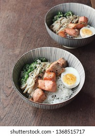Japanese style healthy rice bowl on wooden table. Grilled salmon dice, hard boiled egg, stir-fried golden needle mushroom and okra over rice. Sprinkle with black sesame.