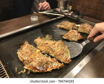Japanese style pancake okonomiyaki handmade and cut on a hot grill at a restaurant. This action shot shows the dish lifted and served with a paddle