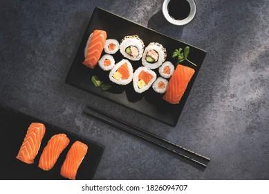Japanese sushi food. Maki and  rolls with spicy tuna, salmon, tofy and  avocado. Top view of assorted sushi, uramaki, hosomaki and nigiri on the stone dark rustic background