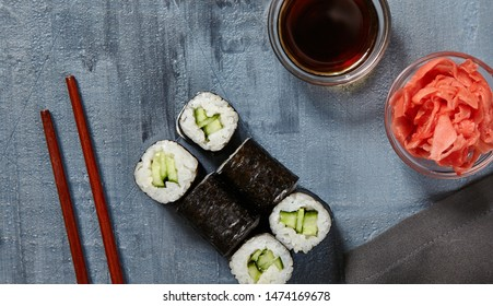 Japanese Sushi - Kappa Maki Sushi Roll (Sushi with Cucumber inside) with Soy Sauce and Ginger over Stone Background. Top View. Japanese Food Concept