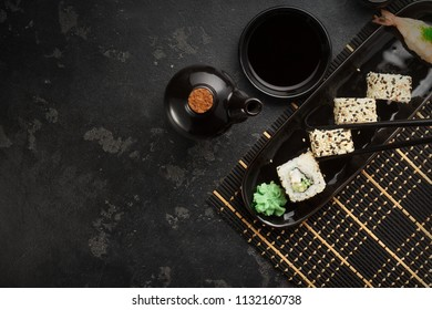 Japanese sushi on a rustic dark background. Sushi rolls, nigiri, maki, pickled ginger, wasabi, soy sauce. Sushi set on a table. Space for text. Top view. Sushi background. Asian or Japanese food frame