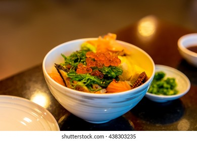 Japanese sushi rice bowl with salmon, salmon roe (ikura), octopus (tako), eel (unagi), yellow tail (hamachi), tamago, ginger and wasabi