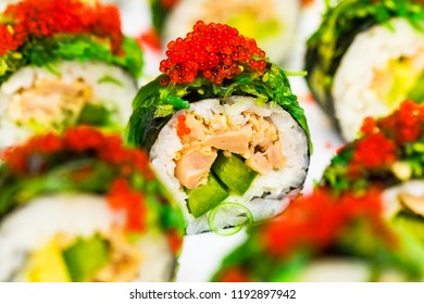 Japanese Sushi Roll with fish, avocado, seaweed topped caviar. Sushi menu. Japanese food. Macro. Selective focus.