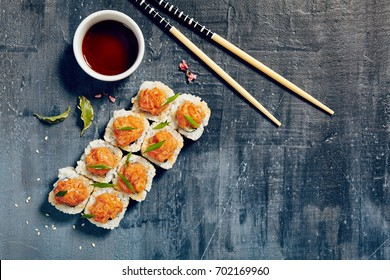 Japanese sushi roll topped with spicy salmon slice on dark grunge background.