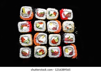 Japanese sushi rolls on black background, top view