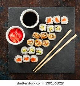Japanese sushi rolls served on stone slate on dark background. Sushi rolls, maki, pickled ginger and soy sauce. View from above. Sushi background. Asian or Japanese food