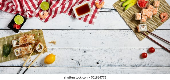 Japanese sushi rolls set with salmon shrimp bonito and cream cheese on bamboo napkin with chopsticks and fresh food ingredients with soy sauce and ginger on white wood copyspace background.
