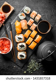Japanese sushi and rolls with soy sauce, ginger and green tea in a teapot. On black rustic background