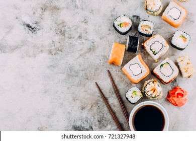 Japanese sushi set on gray stone table background. Sushi rolls, maki, pickled ginger, soy sauce. Copy space Top view. Sushi background. Asian or Japanese food frame