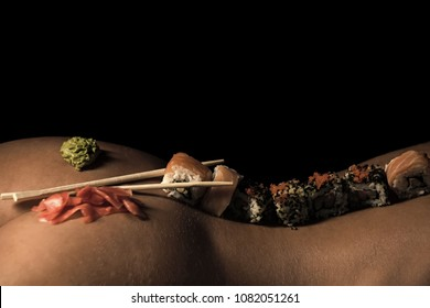 japanese sushi and soy sauce with ginger and wasabi served on sexy female body of woman or girl with stick on back isolated on black background, copy space, food and eating, seduction