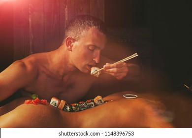 japanese sushi and soy sauce with ginger and wasabi served on sexy female body of woman or girl with stick on back isolated on black background, copy space, food and eating, seduction. Sensual.