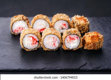Japanese sushi tempura maki crab meat and tobiko roll on  slate. Japanese traditional fusion food style, restaurant menu