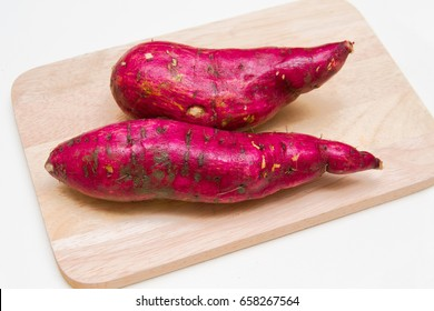 Japanese sweet potatoes on a wooden chopping board.