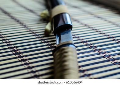 Japanese sword katana on a bamboo mat. Selective focus