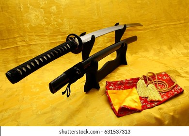 Japanese sword on stand with yellow silk background