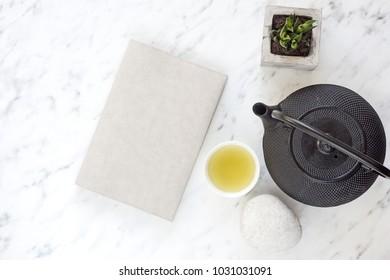 Japanese tea and sketchbook on marble desk